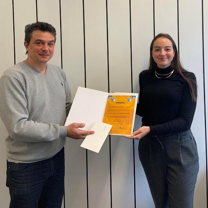 Bild: Prof. Dr.-Ing. Konstantinos Stergiaropoulos überreicht die Urkunde an Sophia Ruppert